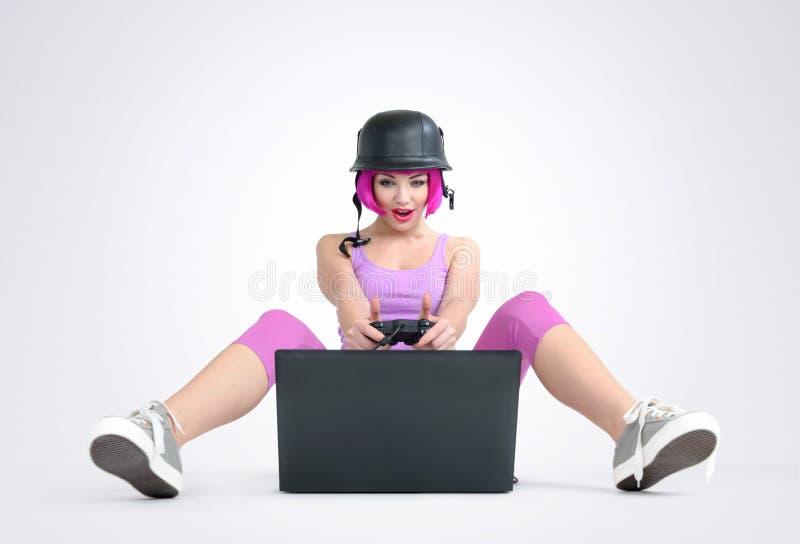 盔甲的女孩与控制杆坐地板和使用比赛在膝上型计算机 免版税库存图片
