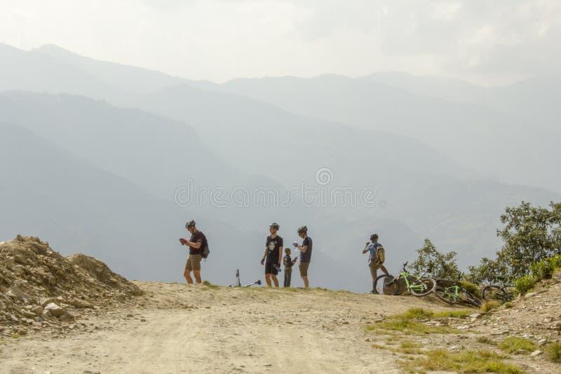 盔甲的骑自行车者在山路放松反对山谷的背景 图库摄影