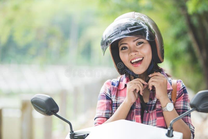 头戴盔甲的年轻亚裔妇女在骑摩托车前  库存照片