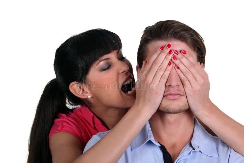 盖一个人的眼睛的妇女 免版税库存图片