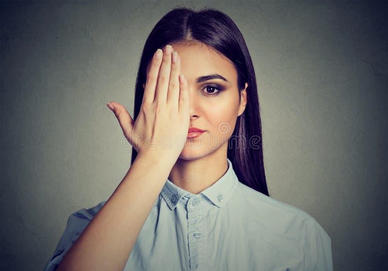 盖一只眼睛的美丽的妇女用手 库存图片