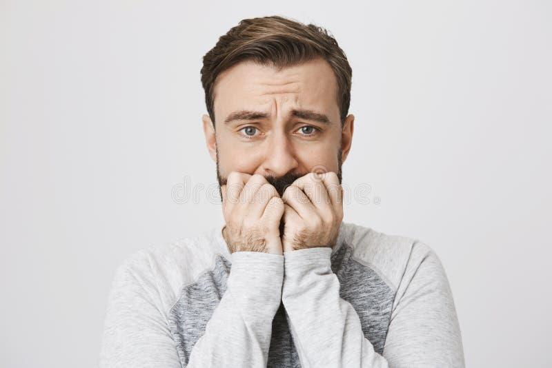 盖他的嘴的一个成人害怕的人的画象与移交白色背景 人是在的害怕的开会 免版税库存照片