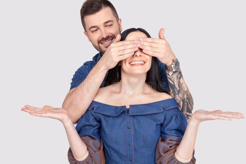 盖他的女朋友眼睛的一微笑的年轻人的画象作为惊奇被隔绝在白色背景 免版税图库摄影