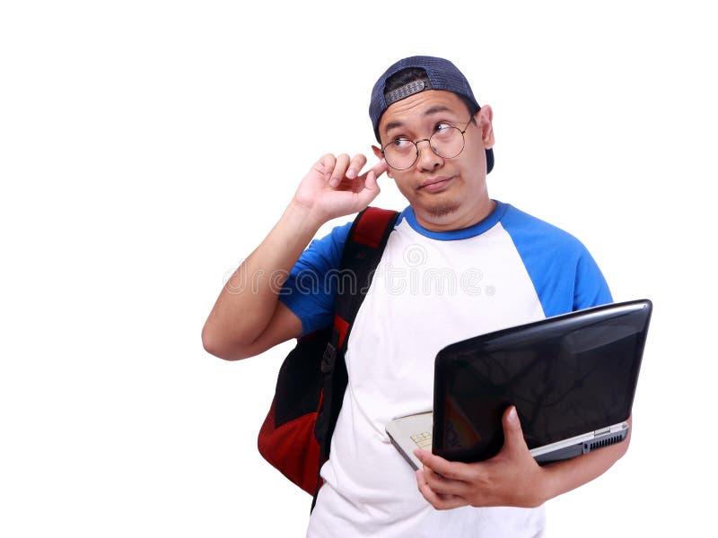 盖他的耳朵的年轻亚裔学生忽略某人 库存图片