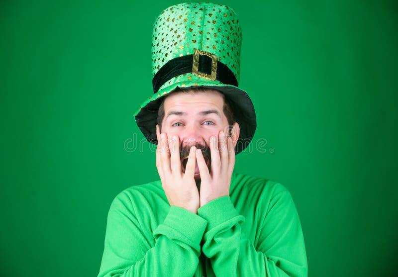 盖他的面孔用手以欢欣 有胡子佩带的绿色的愉快的爱尔兰人 妖精帽子的行家和 库存图片