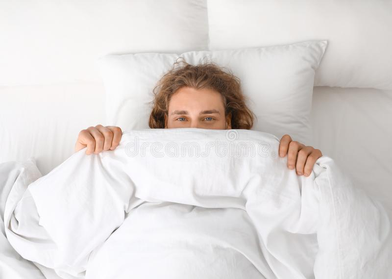盖他的面孔的年轻人用毯子,当说谎在枕头,顶视图时 免版税库存照片