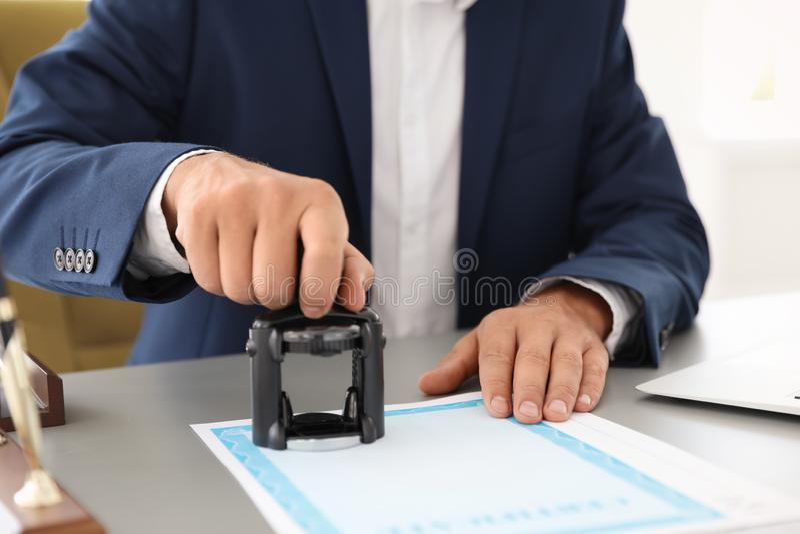 盖印文件的公证员在书桌在办公室 免版税库存照片