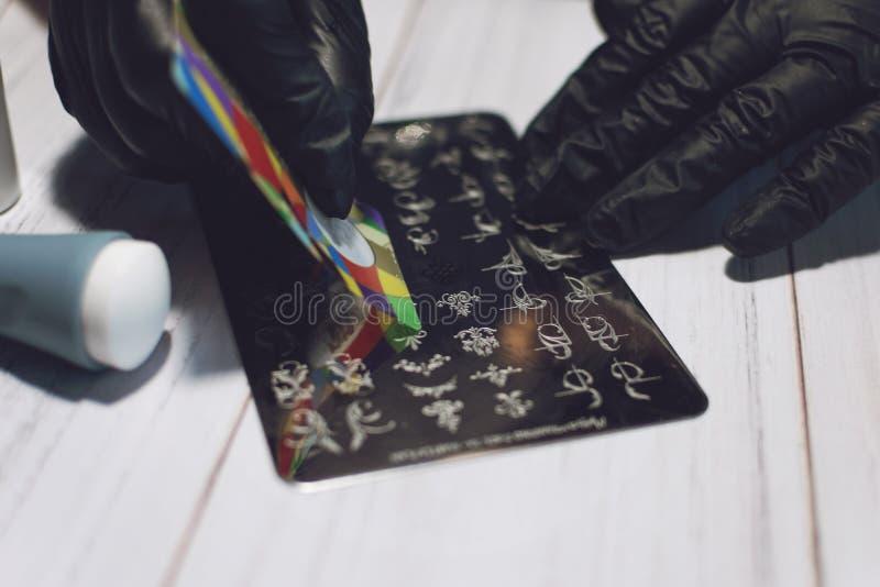 盖印过程的指甲艺术 修指甲大师做盖印与钉子胶凝体擦亮剂,盖印板材和透明模子刮板 库存图片