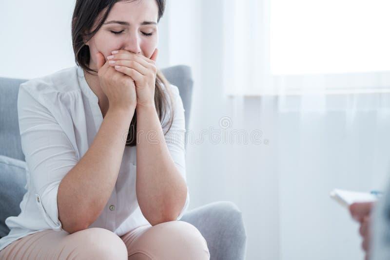 盖她的嘴的哭泣的年轻女人用手,当坐在一间明亮的屋子时 空的空间在背景中 库存图片