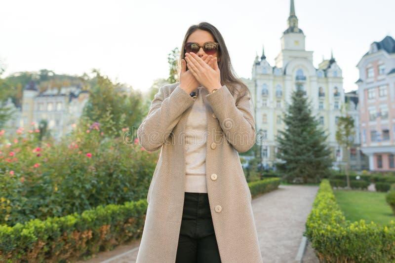 盖她的嘴的年轻女人的室外画象用手 免版税库存照片