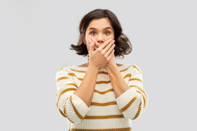 盖她的嘴的震惊年轻女人用人工 免版税库存照片