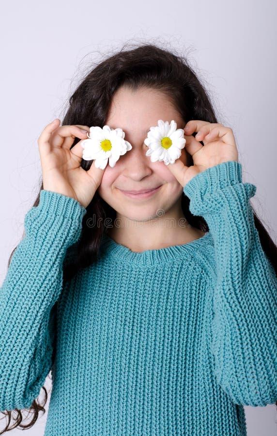 盖她的眼睛的微笑的女孩用花 库存照片