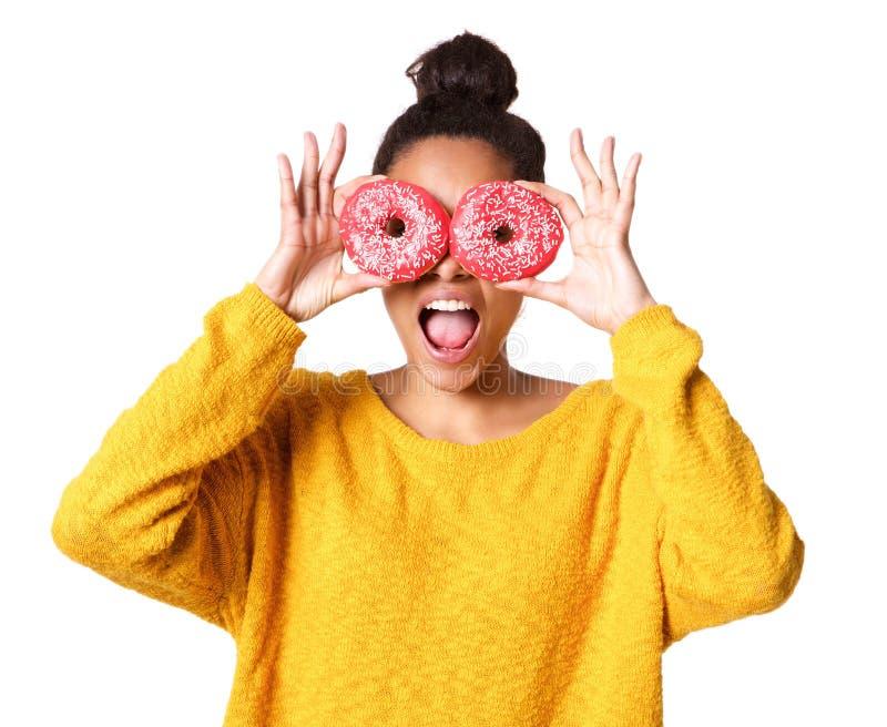 盖她的眼睛的激动的年轻非洲妇女用油炸圈饼 免版税库存照片