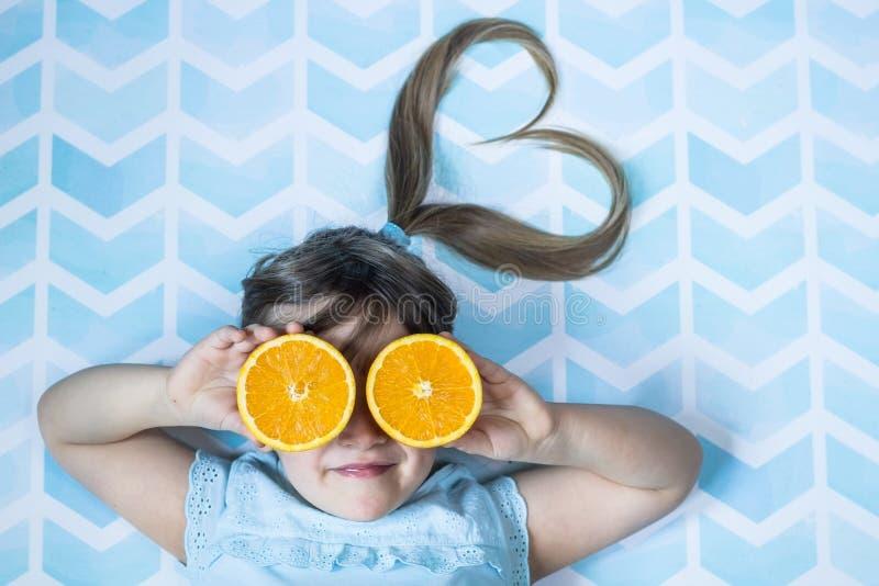 盖她的眼睛的逗人喜爱的小孩女孩用橙色切片 健康概念的食物 免版税库存图片