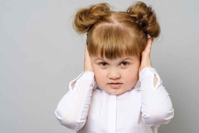 盖她的耳朵的失望的小女孩 库存照片