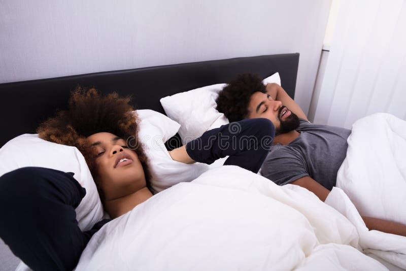 盖她的耳朵的妇女,当打鼾在床上时的人 免版税库存照片