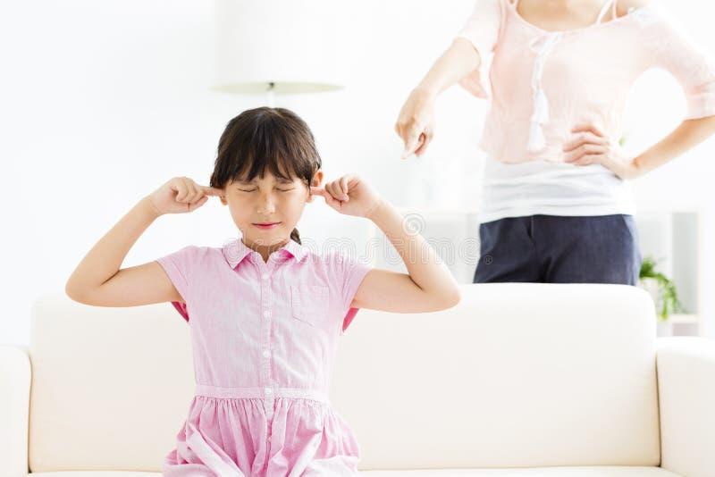 盖她的耳朵的小女孩,当恼怒时她的母亲 库存图片