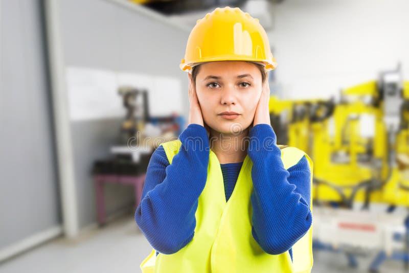 盖她的耳朵的年轻女性工程师 免版税图库摄影