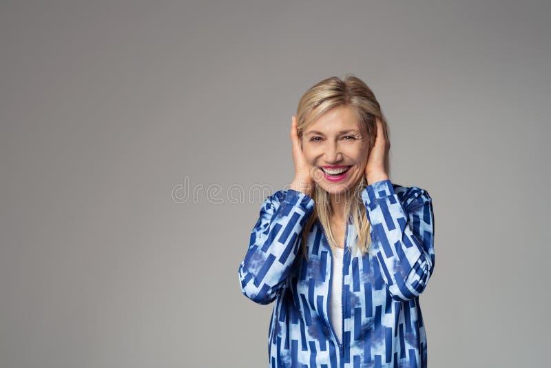 盖她的耳朵的愉快的白肤金发的女实业家 免版税库存图片