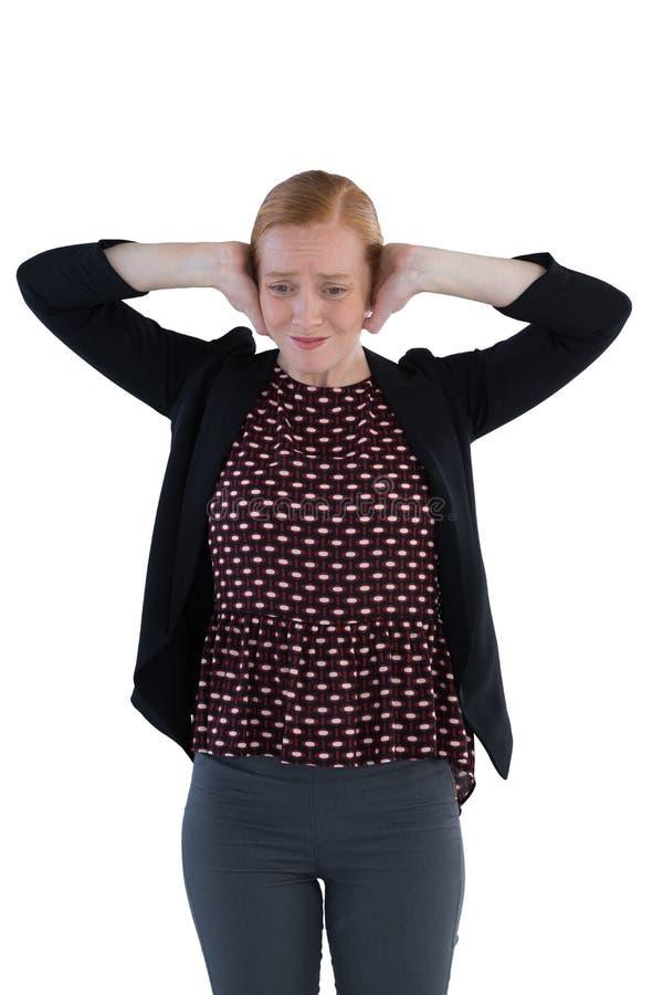 盖她的耳朵的懊恼妇女 免版税库存照片