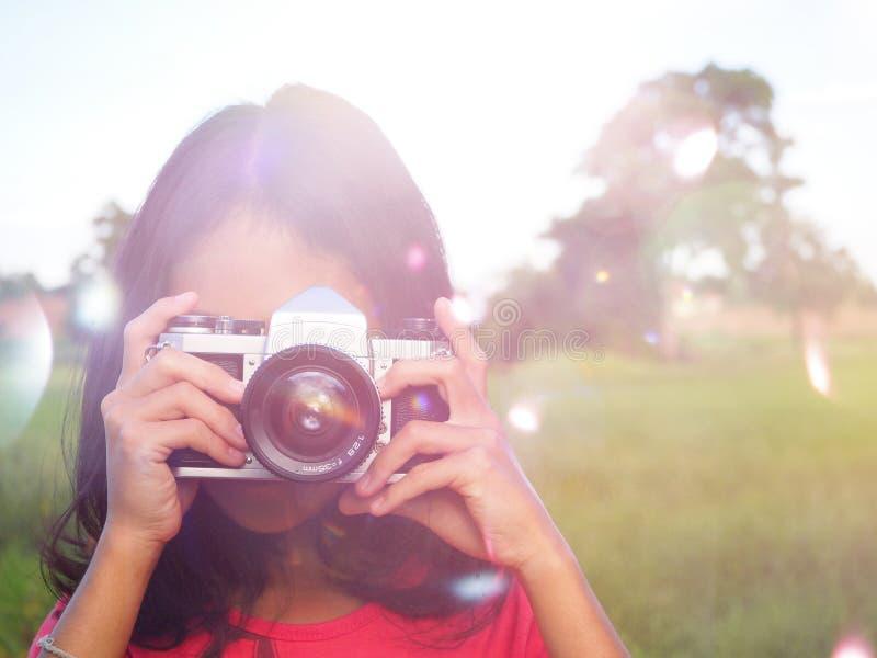 盖她的面孔的女孩摄影师用照相机 图库摄影