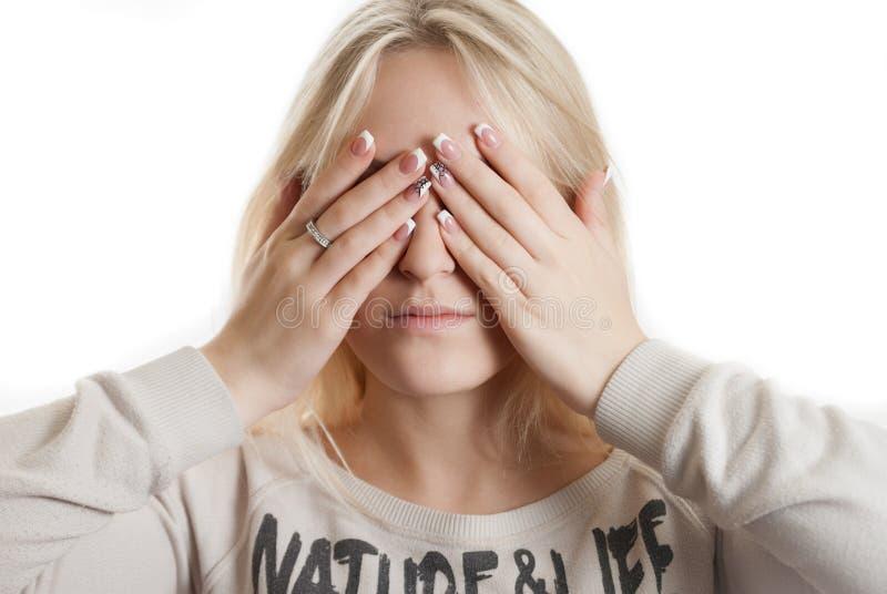 盖她的面孔的女孩由她的手 免版税图库摄影