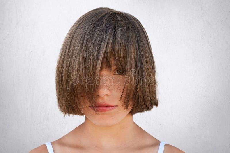 盖她的面孔的小有雀斑的女孩水平的画象用头发,当保持平衡对白色混凝土墙时 Adorabl 图库摄影