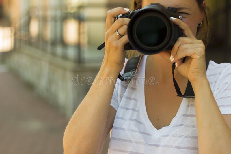 盖她的面孔的摄影师的画象用照相机 摄影师妇女女孩拿着拍摄照片的dslr照相机 免版税库存图片