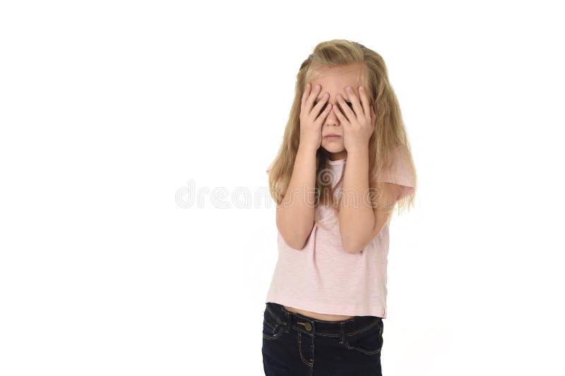 盖她的面孔的甜年轻矮小的女小学生用她的胁迫的手哭泣的哀伤的受害者在学校 库存图片