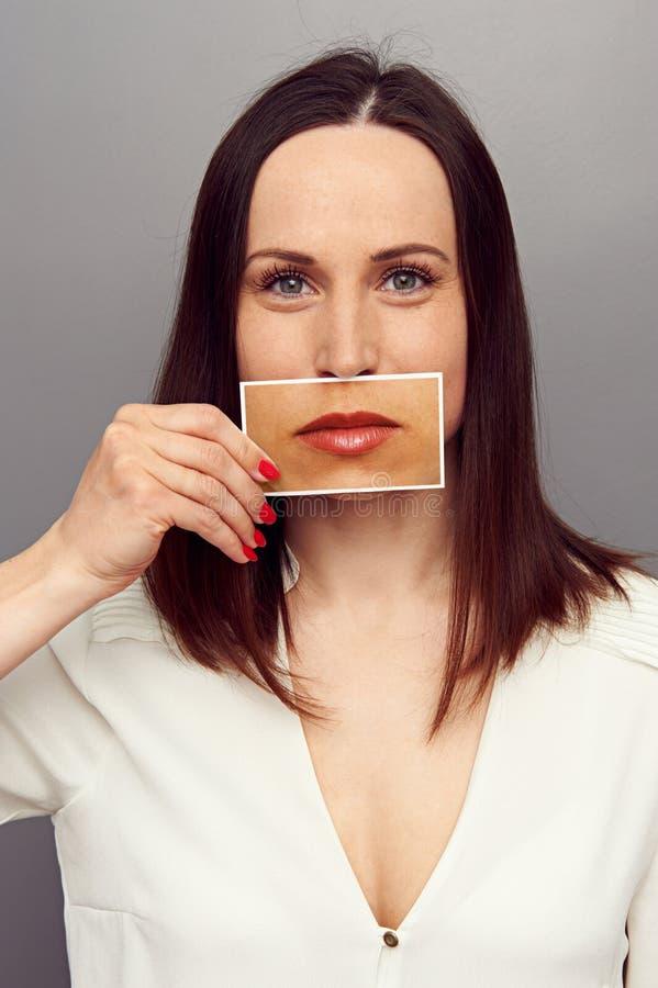 盖她的嘴的妇女用嘴唇图片 免版税库存图片