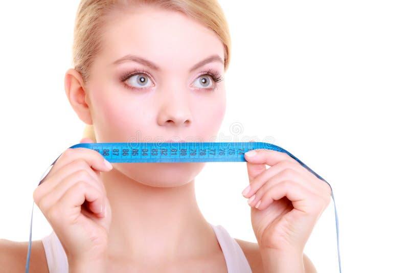 盖她的嘴的适合的妇女用测量的磁带 库存图片