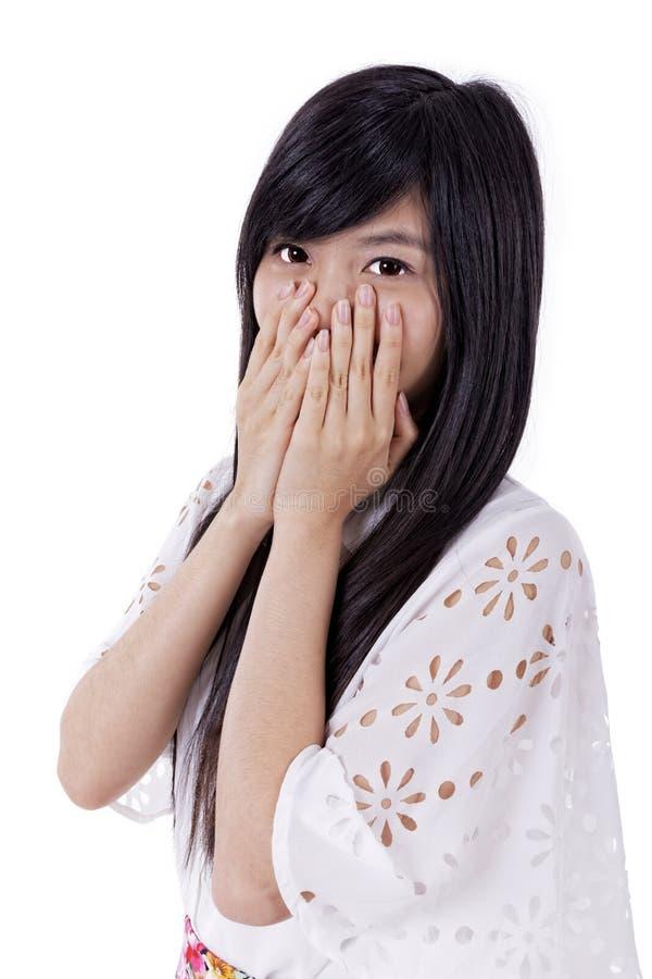 盖她的嘴的年轻亚裔妇女 库存图片