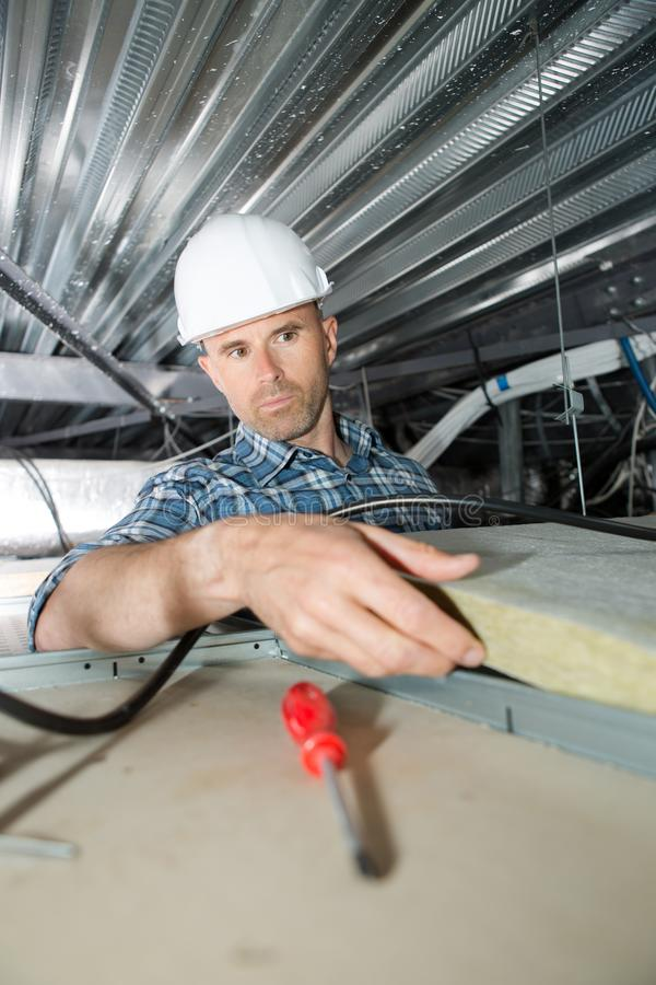 盖屋顶的人安装屋顶绝缘材料的建造者工作者 免版税库存照片