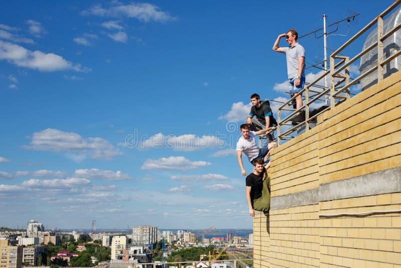 盖屋顶的人小组上升到屋顶 图库摄影
