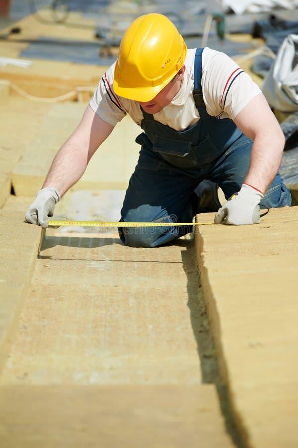 盖屋顶的人工作者测量的绝缘材料 免版税库存图片