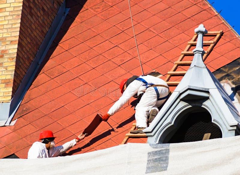 盖屋顶的人工作 库存照片