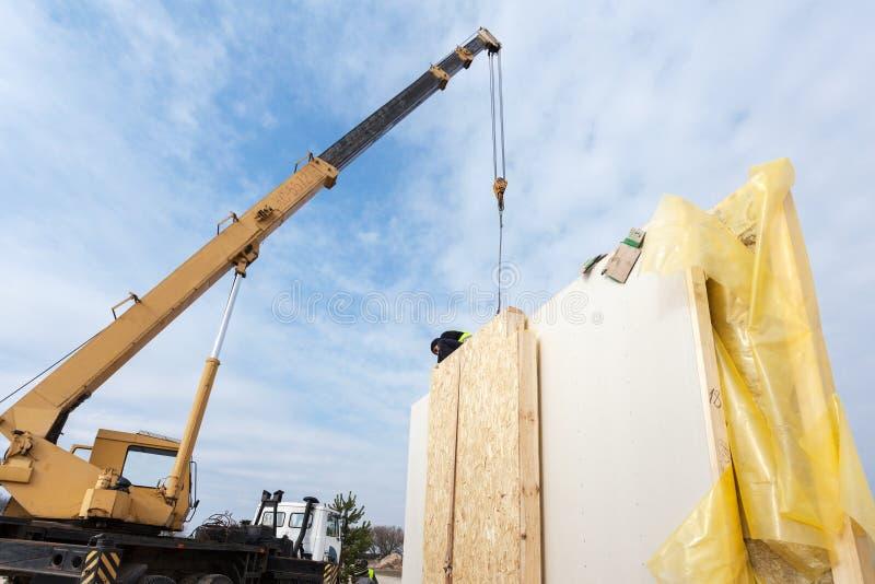 盖屋顶的人有安装结构被绝缘的盘区SIP的起重机的建造者工作者 修造的新的框架省能源的房子 免版税库存照片