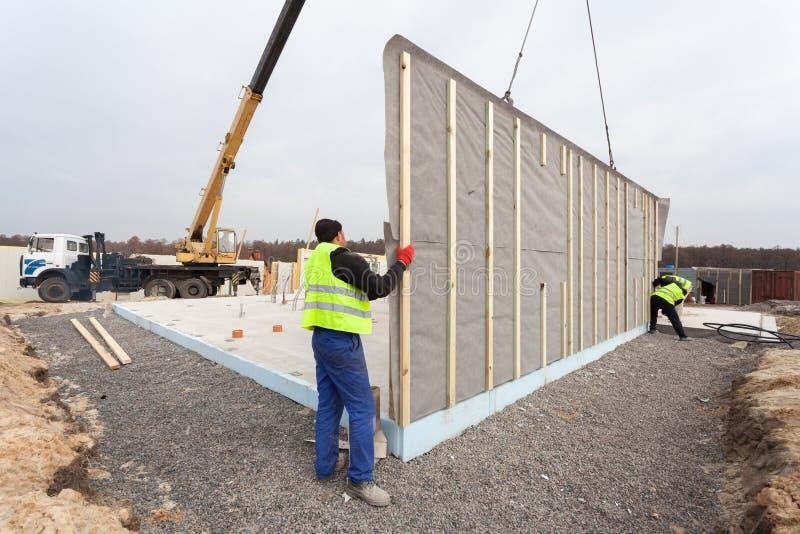 盖屋顶的人有安装结构被绝缘的盘区SIP的起重机的建造者工作者 修造的新的框架省能源的房子 库存照片