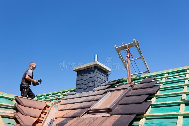 盖屋顶的人运载的瓦片 图库摄影