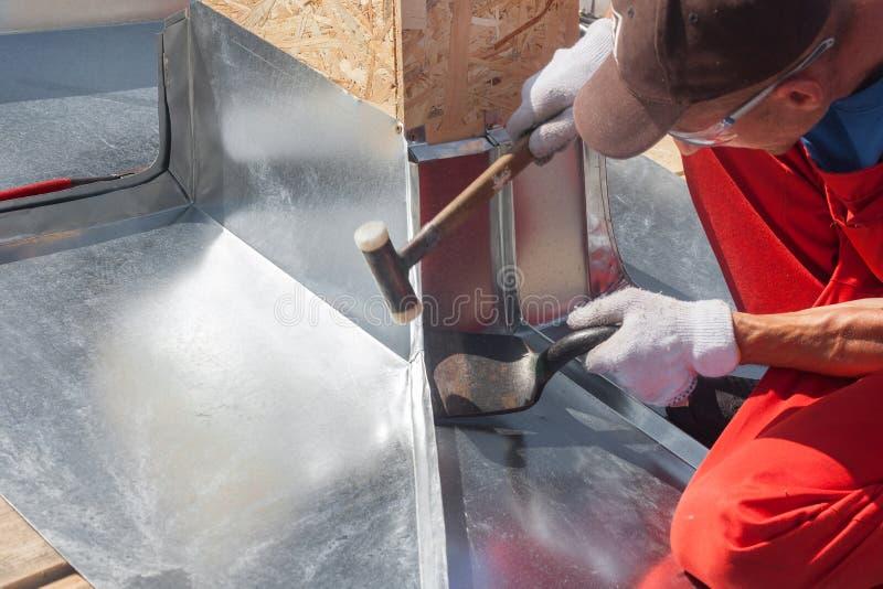 盖屋顶的人建造者折叠金属板的工作者精整使用橡胶短槌 库存图片
