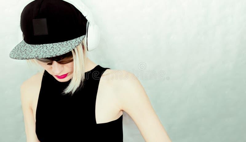 盖帽和时髦的耳机的DJ女孩 库存照片