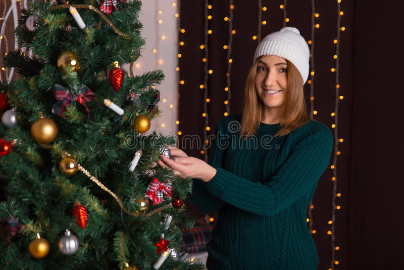 盖帽和毛线衣的美丽的女孩装饰一棵圣诞树 库存图片