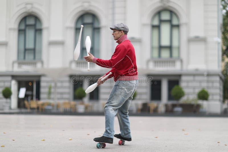 盖帽的一个人玩杂耍与在街道上的俱乐部 免版税库存照片