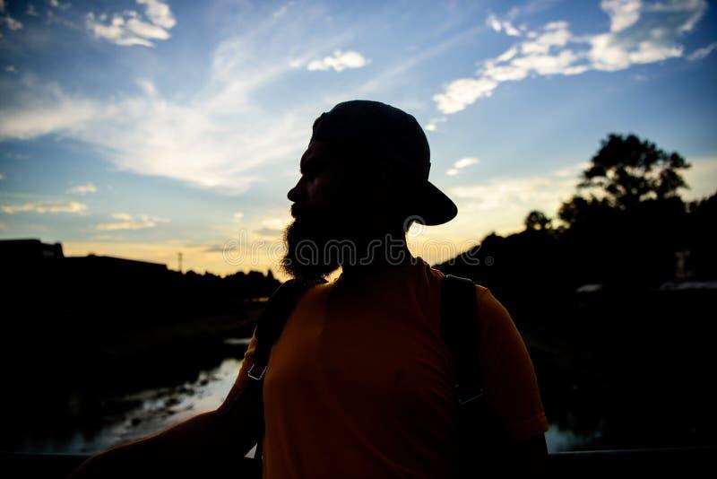 盖帽的人享受日落,当在桥梁时的立场 享受宜人的片刻 在蓝天前面的人在晚上时间敬佩 免版税库存图片