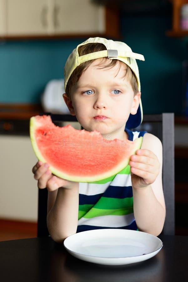 盖帽的四岁的男孩吃一个西瓜在厨房用桌上 免版税图库摄影
