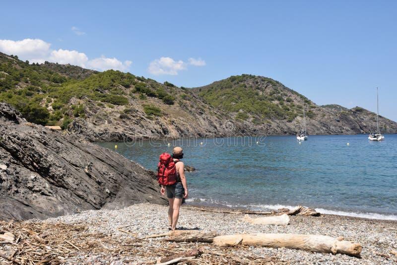 盖帽的在La Taballera海滩的de Creus,肋前缘远足者妇女 库存照片
