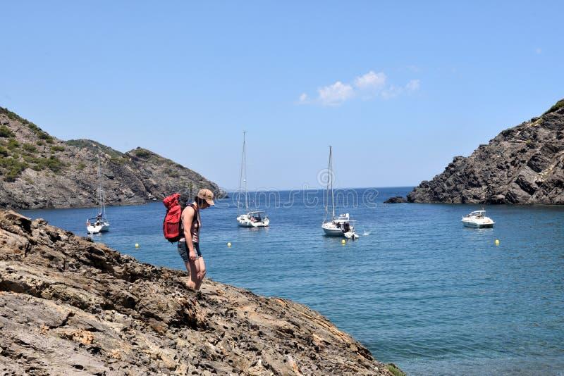 盖帽的在La Taballera海滩的de Creus,肋前缘远足者妇女 免版税图库摄影