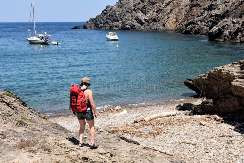 盖帽的在La Taballera海滩的de Creus,肋前缘远足者妇女 免版税库存照片