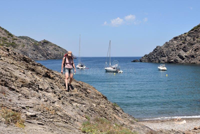 盖帽的在La Taballera海滩的de Creus,肋前缘Brava,希罗纳省远足者妇女 免版税库存图片
