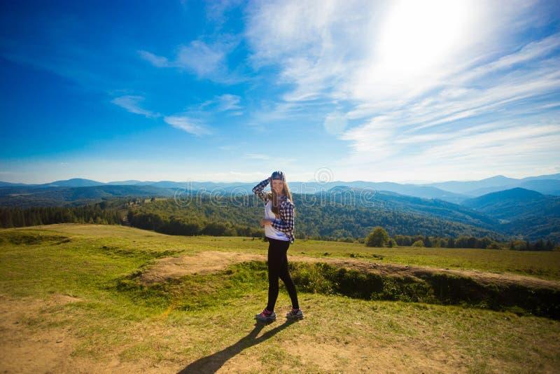 盖帽的妇女游人在小山顶部享受山的看法  库存照片